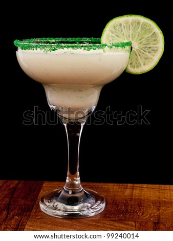 fresh cocktail served on a bar top garnished with green sugar and a lime wheel isolated on a black background