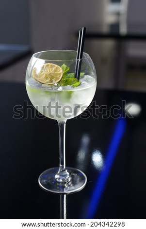 Fresh cocktail with ice, mint and lime on the dark background