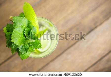 Fresh cocktail with mint on the wooden background. Shallow depth of field. - stock photo