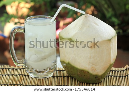 Fresh coconut and a cup of the juice - stock photo