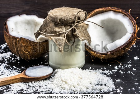 Fresh coconut and coconut oil in rustic jar - stock photo