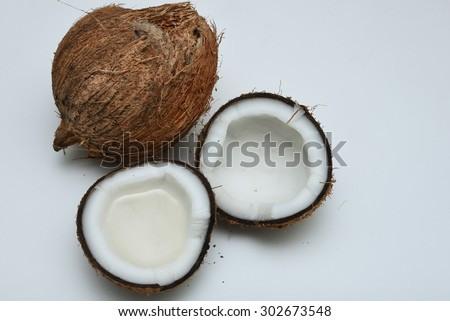 Fresh coconut cut open in half with extra clear and pure cooking/massage coconut oil filled in open coconut for alternative therapy spa. Whole coconut Malaysia - stock photo