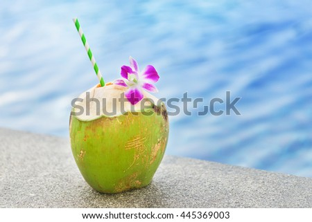 Fresh coconut drink with orchid flower near swimming pool