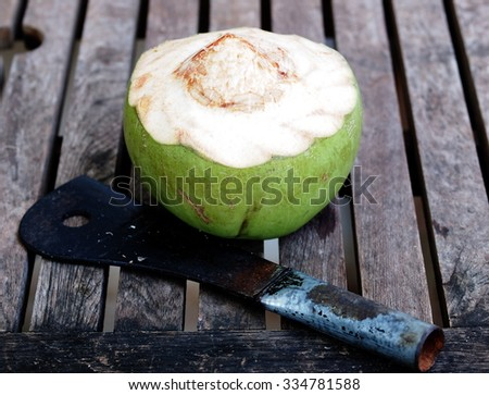 fresh coconut, half shelled, organic natural drink in colorful green shell on a wooden table outdoor under morning sunlight with a hand made black steel chop knife ready to serve. - stock photo