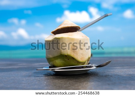 Fresh coconut in plate on the beach near sea - stock photo