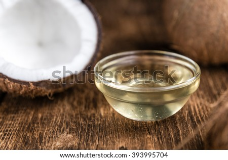 Fresh Coconut Oil(detailed close-up shot; selective focus) on wooden background - stock photo