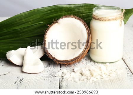 Fresh coconut oil in glass bottle and green leaf on color wooden table background - stock photo