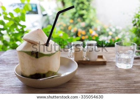 fresh coconut water drink on wooden table with natural blur background