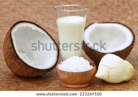 Fresh Coconut with milk in a glass on textured surface - stock photo