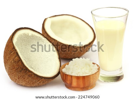Fresh Coconut with milk in a glass over white background - stock photo