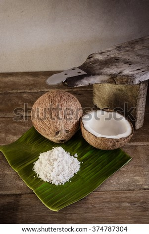 fresh coconuts and coconut flakes on banana leaf and old coconut grater