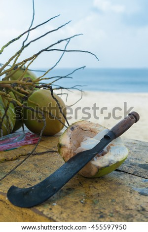 Fresh coconuts opened by a machete on a beautiful tropical beach,