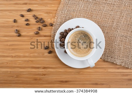 Fresh coffee beans on wood and linen - stock photo