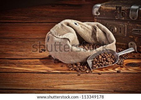 Fresh coffee beans on wood and linen bag, ready to brew delicious coffee - stock photo
