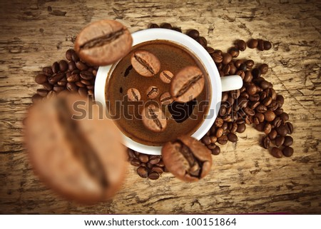 Fresh coffee beans with cup on wood - stock photo