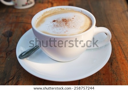 Fresh  Coffee in a White Ceramic Cup with chocolate on top