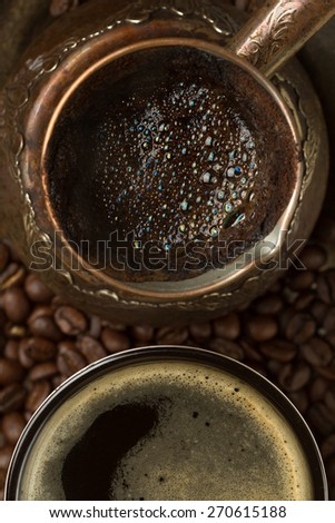 Fresh coffee in coffee pot and cup (top view, close-up) - stock photo