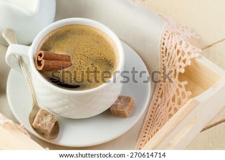 Fresh coffee with cinnamon and sugar (close-up) - stock photo