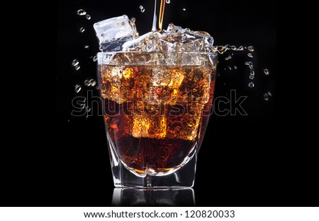 Fresh cola drink background with ice and splash on a black