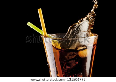 fresh cola juice and ice cubes splash in a glass on black background