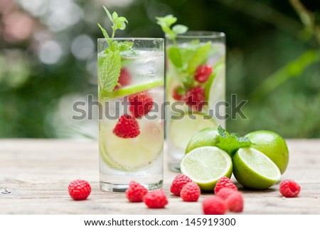 fresh cold drink water ice cubes peppermint lime raspberry outdoor summer - stock photo