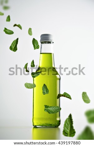 Fresh cold green lemonade in rustic sealed glass bottle isolated on white, mint leaves flying in air across, commercial retail picture - stock photo