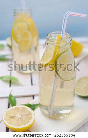 Fresh cold lemon drink with slices of lime and lemon - stock photo