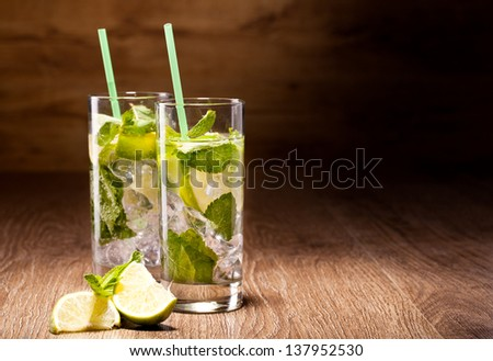 Fresh cold Mojito Cocktail on a wooden background - stock photo
