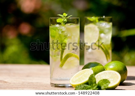 fresh cold refreshment drink mineral water soda with lime and mint on wooden table in summer - stock photo