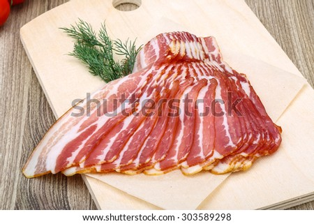 Fresh cold sliced bacon with dill branch on the wood background