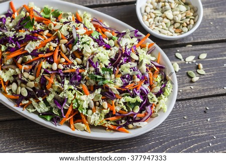 Fresh Cole slaw with pumpkin, flax, sesame seeds and pine nuts - delicious healthy vegetarian food. On a dark rustic wooden background