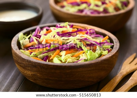 Fresh coleslaw salad made of shredded red and white cabbage and carrot, served in wooden bowl with sauce in the back, photographed with natural light (Selective Focus, Focus one third into the salad)
