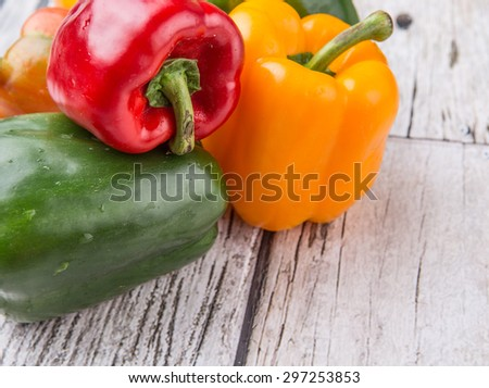fresh colorful bell peppers on a rustic wooden background