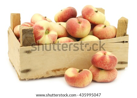 fresh colorful flat peaches (donut peaches) in a wooden crate on a white background