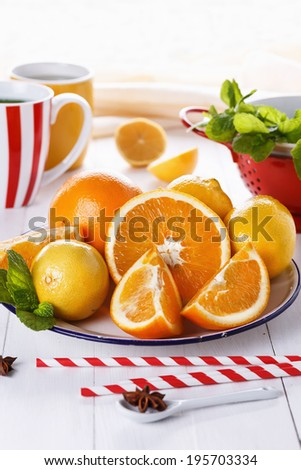 Fresh colorful oranges, lemons and mint over white wooden background. Selective focus, shallow DoF - stock photo