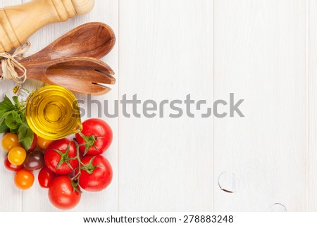 Fresh colorful tomatoes, basil and olive oil on white wooden table. Top view with copy space - stock photo