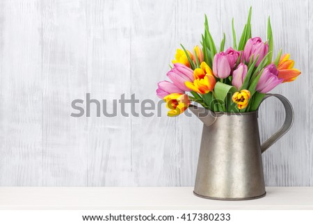 Fresh colorful tulip flowers bouquet on shelf in front of wooden wall