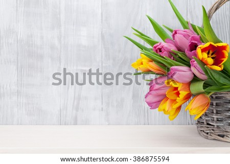Fresh colorful tulip flowers bouquet on shelf in front of wooden wall. View with copy space - stock photo