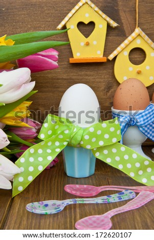 Fresh colorful tulips and boiled eggs in colorful cups for easter