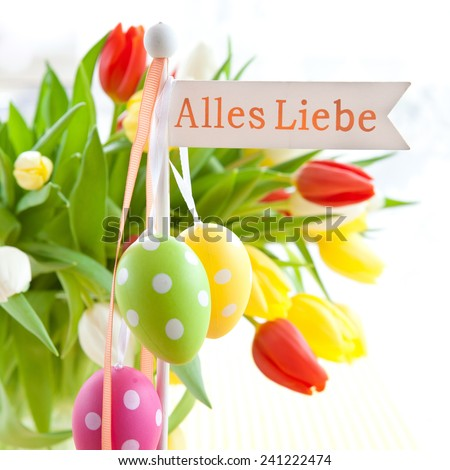 Fresh colorful tulips with a Alles Liebe tag - stock photo