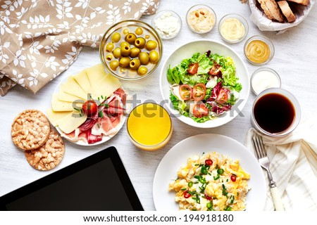 Fresh continental breakfast. Healthy food. Tablet, black screen. Scrambled eggs, salad, cheese, prosciutto, coffee and juice. Concept of business or holiday breakfast. Top view. - stock photo