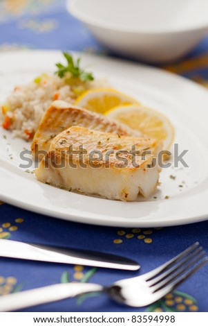 Fresh cooked cod fish with rice and lemon - stock photo