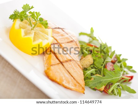 Fresh cooked salmon fillet with arugula salad - stock photo