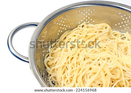 Fresh cooked spaghetti in stainless strainer on white  - stock photo