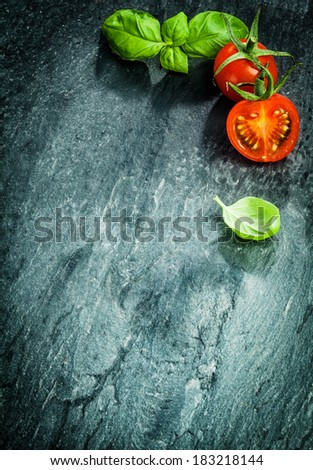 Fresh cooking ingredients with basil and tomato forming a corner border on a darked cracked and texture surface with copyspace and vignetting - stock photo