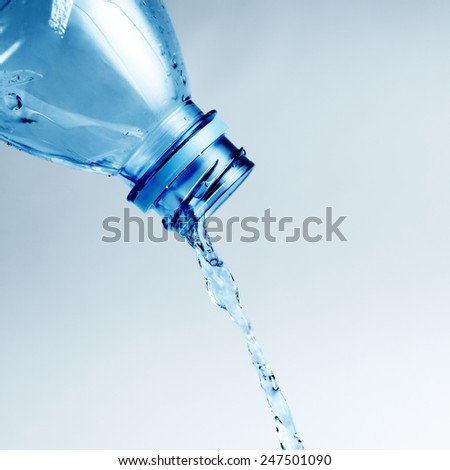 Fresh cool water pouring from a clean plastic water bottle - stock photo