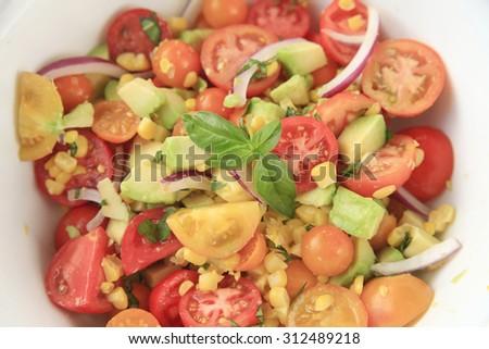 Fresh corn, avocado and cherry tomatoes with basil - stock photo