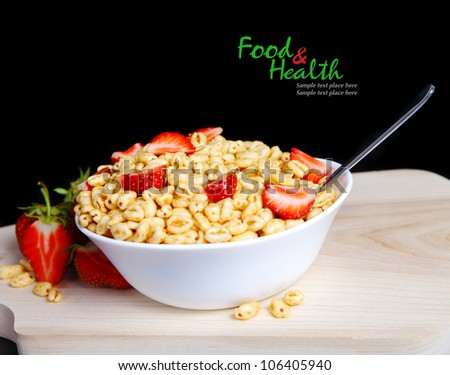 Fresh corn flakes with strawberries close up isolated on black