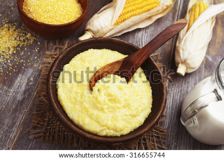 Fresh corn meal in the plate on the table - stock photo