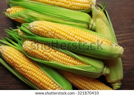 Fresh corn on cobs on wooden table, closeup - stock photo